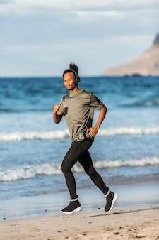 海の近くを実行しているヘッドフォンでアフリカ系アメリカ人の男