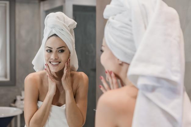 陽気な女性のシャワー後の顔に触れる