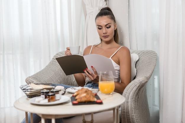 Женщина читает журнал во время завтрака