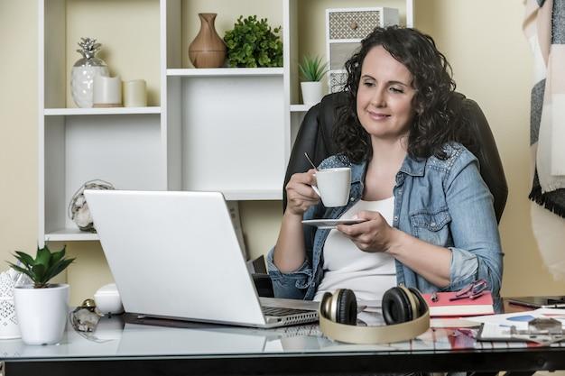 Взрослая довольная женщина пьет вкусный напиток и смотрит видео на ноутбуке дома