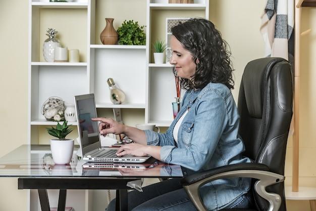 Взрослая женщина, использующая ноутбук с удовольствием в светлой современной квартире