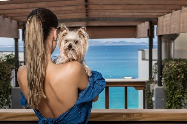 Анонимная женщина обнимает собаку на террасе отеля