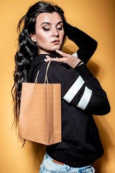 幸せなブルネットの少女は、オレンジ色の背景にクラフトバッグで購入を保持しています。