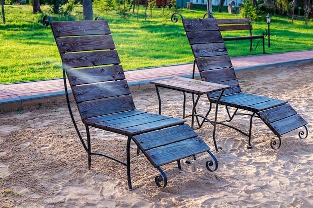 休憩ゾーン。木製のサンラウンジャーとテーブル付きの椅子は、湖に面した湖のそばのビーチに立ちます。
