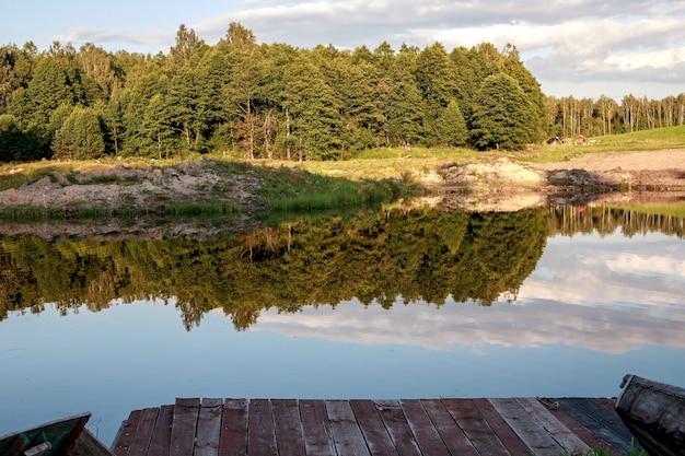Зона отдыха. голубая вода в лесном озере с соснами. лес отражается в воде.