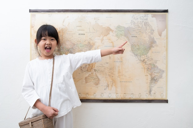 子供が世界の地図を指差して笑っています。