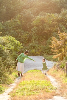 В парке на закате мама и ребенок веселятся.