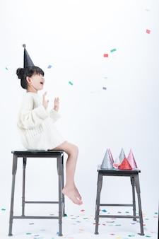黒いパーティの帽子をかぶった子供が椅子に座って、母親が投げる色紙の粉を見て楽しんでいます。