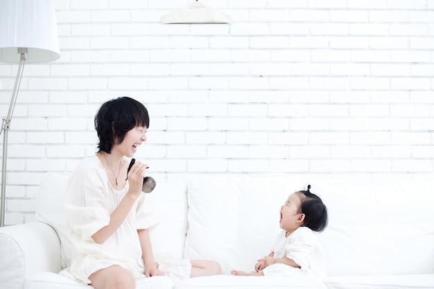 母親と赤ちゃんはお互いに向き合い、楽しいゲームをします。
