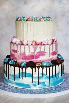 Трехъярусный цветной торт с цветными пятнами шоколада на свету.