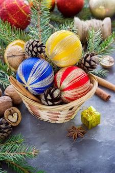 暗い表面にクリスマスの属性とプレゼントボックスがいっぱい入ったバスケット。クリスマスの組成