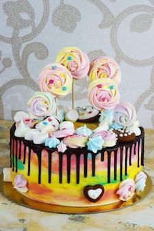 木製のメレンゲと白の子供のケーキ虹色