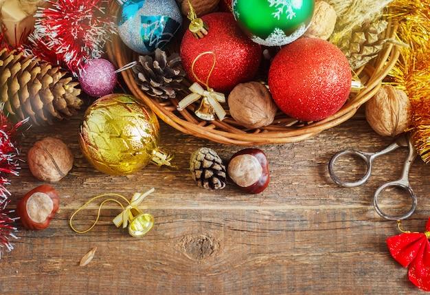 Рождественская композиция с подарками. корзина, красные шары, сосновые шишки, снежинки на