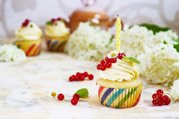クリームとベリーとキャンドルのカップケーキ