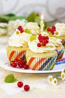 クリームとベリーとキャンドルでお祝いカップケーキ