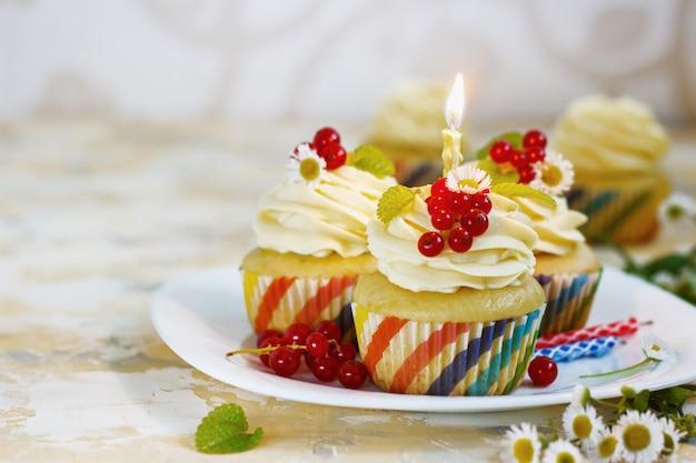 クリーム、ベリー、キャンドル入りの優しいお祝いカップケーキ