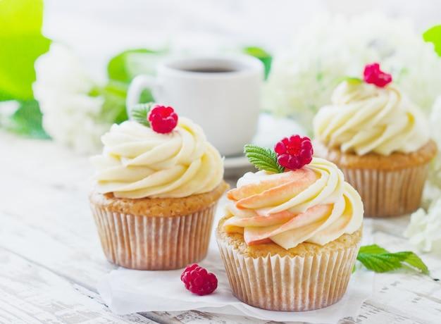 クリームとラズベリーの白い木の繊細なバニラカップケーキ