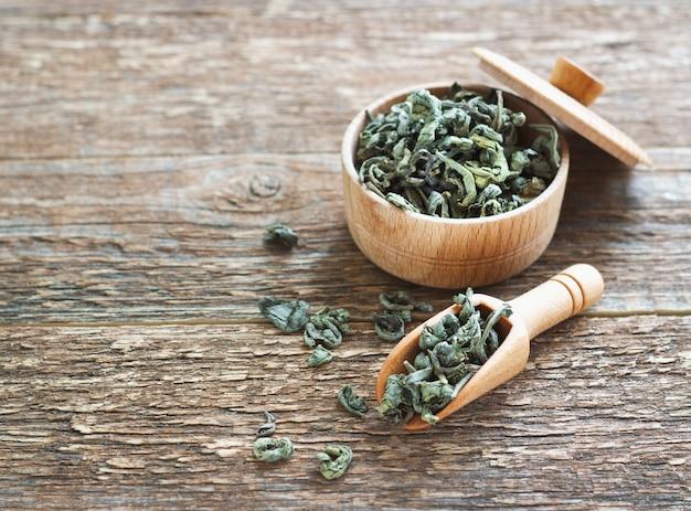 木製の背景に乾燥緑茶のスプーンを残します