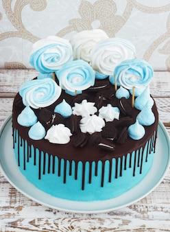 メレンゲとチョコレートが付いた子供用ブルーケーキ