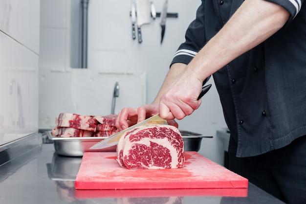 リブアイ霜降り牛ステーキの部分を切る人