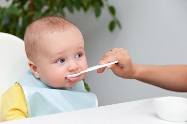 Маленький мальчик в цветной одежде ест йогурт из ложки, грязный рот