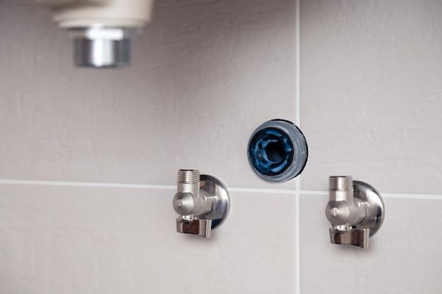 アクアストップ、バルブソケット、切り込み、分岐、タイル壁、タイル張りのバスルームの固定シンク。専門の配管修理サービス、水道管の設置、下水道排水管の設置