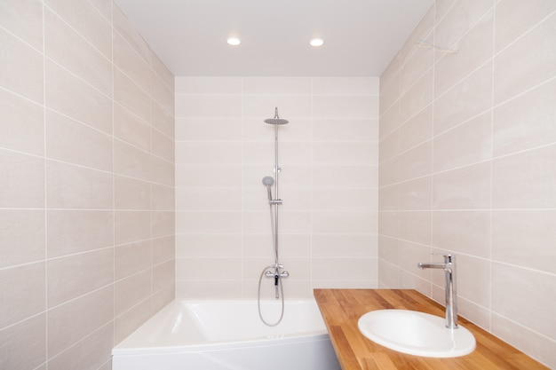 Пустая новая ванная комната с бежевой керамической прямоугольной плиткой, большая ванна, серебряный душ, водопроводный кран, деревянная столешница с керамической раковиной. ремонт ванной комнаты, ремонт в квартирах, гостиница