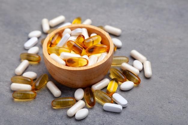 Разные таблетки в деревянной миске