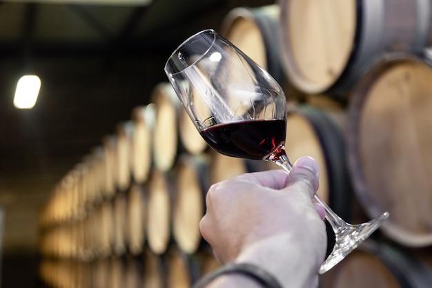 背景の木製オーク樽に赤ワインのグラスとクローズアップ手は、ワイナリーの古いセラーの順序でまっすぐな行に積み上げられました。