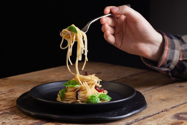 Макароны спагетти с овощами, перцем, листьями базилика на черной круглой тарелке на коричневом деревенском старинных деревянных фоне