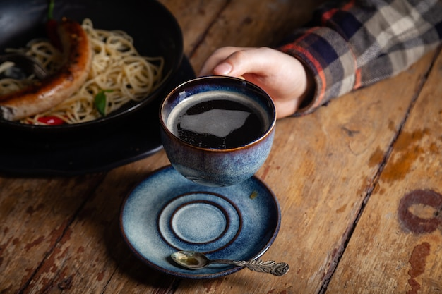 手で黒いアメリカーノコーヒーカップを持つ孤独な男