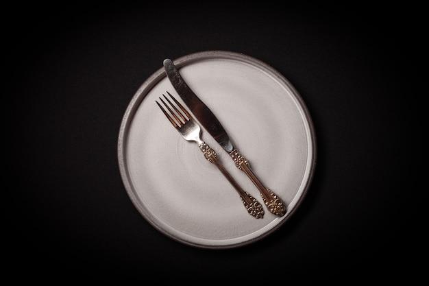 ビンテージキュプロニッケルフォークとナイフで黒の背景に空の丸い灰色セラミックプレート