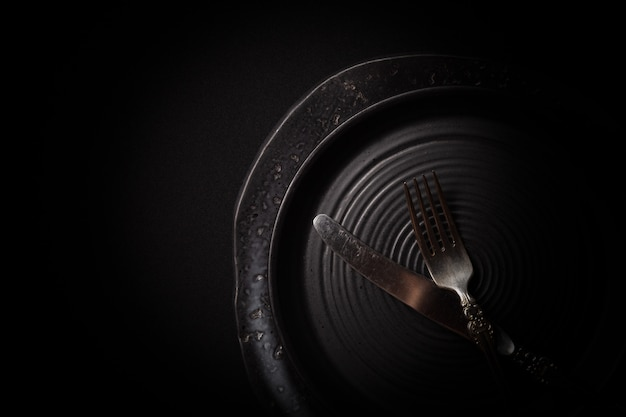 空のラウンド黒熟成セラミックプレートとビンテージカトラリー