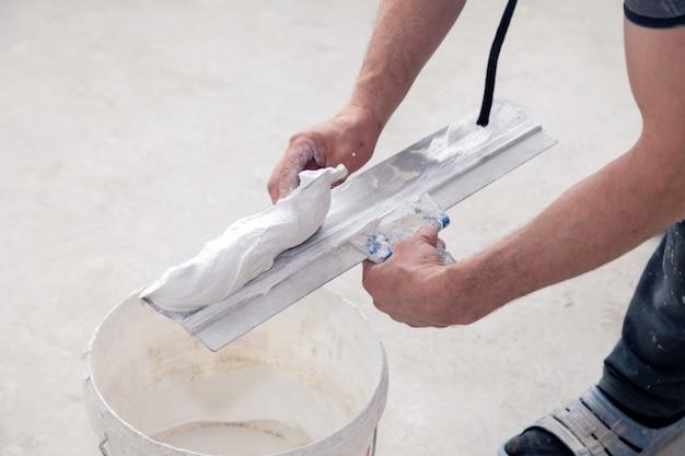 Работник, держа шпатель с раствором замазки. строитель кладет штукатурку в шпатель в ведро