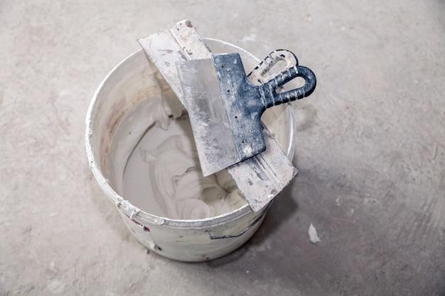 Цементная штукатурка и шпатели в строительном ведре