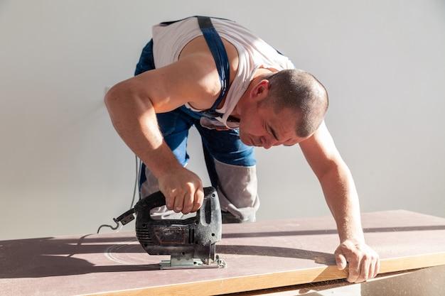 Рабочий с профессиональным режущим инструментом резал деревянную столешницу