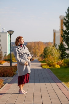Кавказский красивая счастливая беременная женщина, одетая в юбку, серое пальто, касаясь ее живот