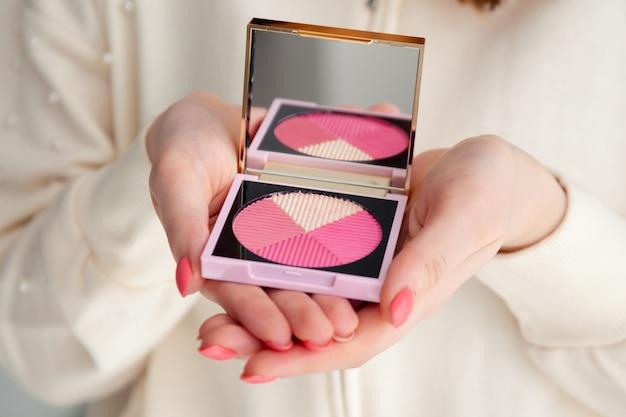 鏡で修正彫刻パレットピンク赤面を保持しているマニキュアで女性の手をクローズアップ。