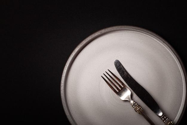 Крупным планом пустая круглая серая керамическая тарелка на черном фоне