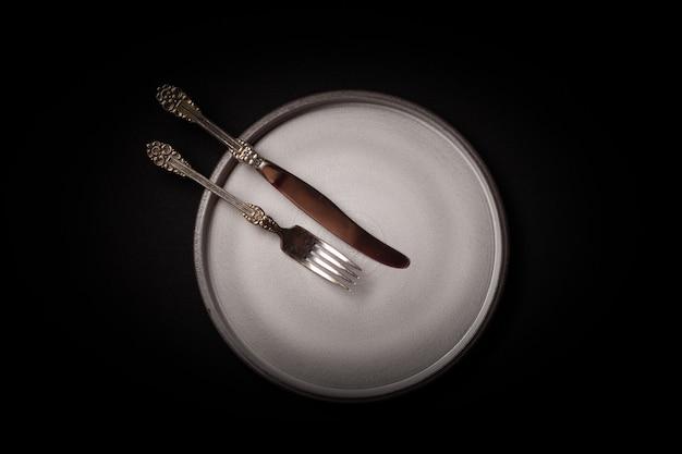 Пустая круглая серая керамическая тарелка на черном фоне, винтажная вилка, нож