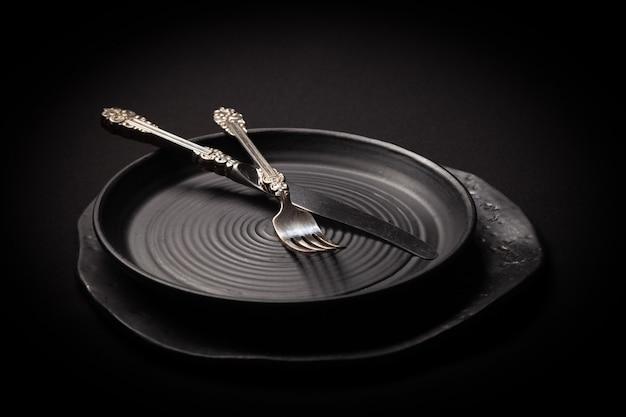 Крупным планом пустые круглые черные керамические тарелки, серебряная вилка, нож на темном фоне