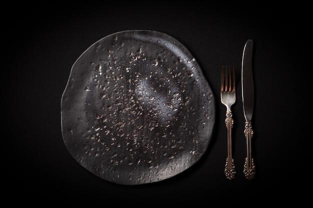 Крупным планом пустой круглый черный возрасте керамическая тарелка, старинные вилки, нож на темном фоне
