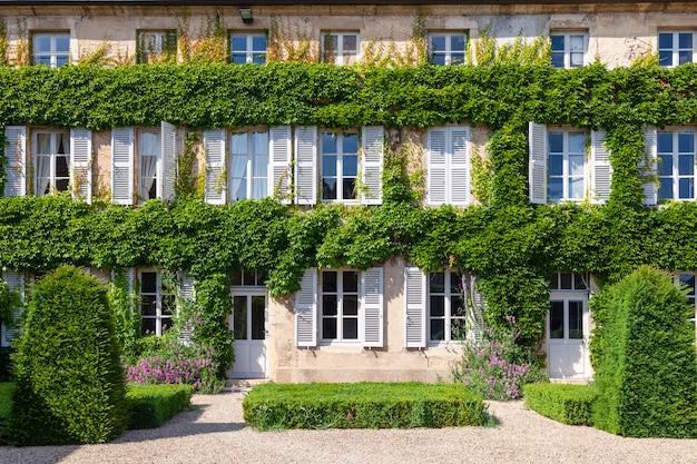 美しいれんが造りの家、白い木製シャッター付きの窓