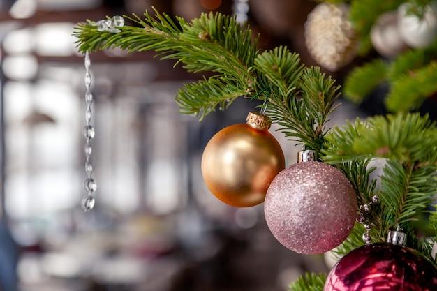 Украшение рождества нового года крупного плана, ветви ели елевые с шариками сияющих праздничных игрушек золотыми и розовыми.