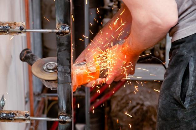 Рабочий режет металл с угловой шлифовальной машиной