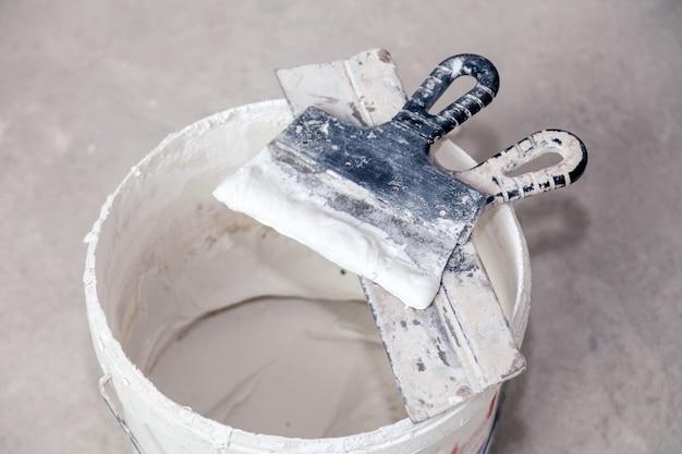 Цементная штукатурка и шпатель, ведро