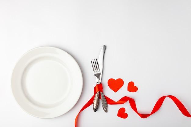赤テープで結んだ皿とカトラリー
