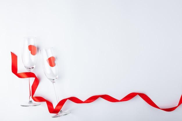 バレンタインデーディナーロマンチックなお祭りの設定、赤テープ、シャンパンワイングラス、ボトル、白い木製の背景にハート。コピースペース、テキストのための場所。上面図。