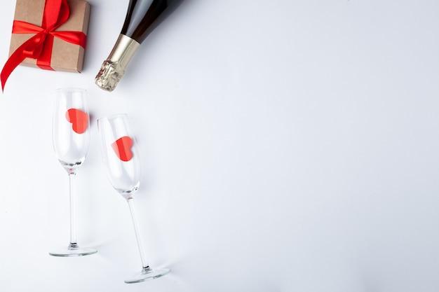 バレンタインデーディナーロマンチックなお祭りの設定、赤テープ、クラフトギフトボックス、シャンパンワイングラス、ボトル、白い木製の背景にハート。コピースペース、テキストのための場所。上面図。