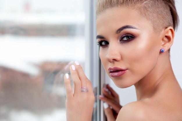 明るい化粧と剃ったこめかみの短い髪のクローズアップの肖像画セクシーな金髪モデル。